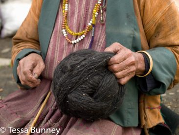 A Brokpa woman holding a ball of yak hair spun using a drop spindle called a yoekpa in the remote village of Merak in Eastern Bhutan. The Brokpa, the semi-nomads of the villages of Merak and Sakteng are said to have migrated to Bhutan a few centuries ago from the Tshona region of Southern Tibet. Thriving on rearing yaks and sheep, the Brokpas have maintained many of their unique traditions and customs.
